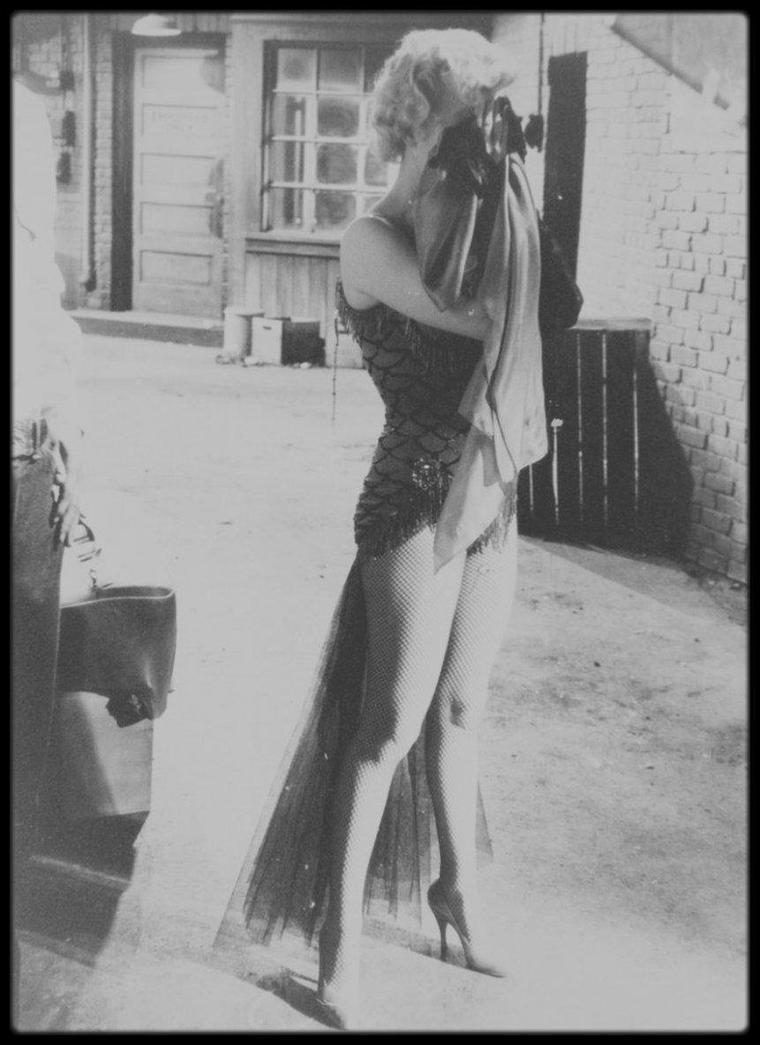 """1956 / Marilyn et Don MURRAY sur le tournage du film """"Bus stop"""", Marilyn campant Chérie, une danseuse de saloon, chantant """"That old black magic"""" dans un costume signé TRAVILLA sous l'objectif du photographe Milton GREENE."""