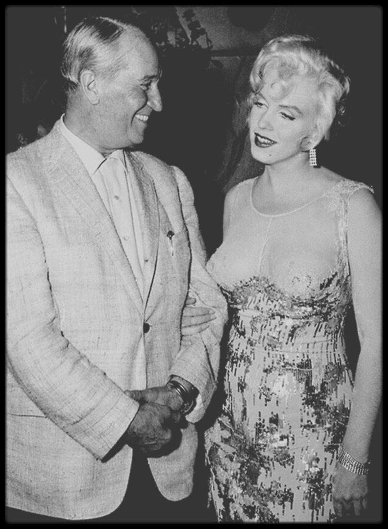 """1958 / Rencontre avec le """"French-lover"""" Maurice CHEVALIER, sur le plateau du film """"Some like it hot"""", dans les studios de la M.G.M. ; En cette année 1958, Maurice CHEVALIER est de retour sur le devant de la scène hollywoodienne avec le succès critique et publique de l'adaptation cinématographique de l'oeuvre de Colette : « Gigi » de Vincente MINNELLI. Lors des Oscars 1959, ce film remportera 9 statuettes. Sa carrière est relancée. La rencontre est joyeuse et semble faire grand plaisir à Marilyn. Se trouve également alors sur le plateau, Billy WILDER, le réalisateur de """"Some like it hot"""". Rappelons que 3 ans plus tôt, en 1955, Marilyn fit une session photos avec l'acteur chanteur sous l'objectif de Milton GREENE."""