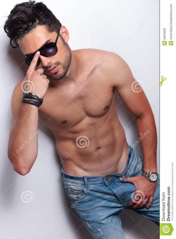 Le jeune homme de torse nu ajuste ses lunettes de soleil